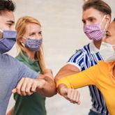 Vier junge Leute mit Mund-Nasen-Maske machen einen Ellbogen-Check