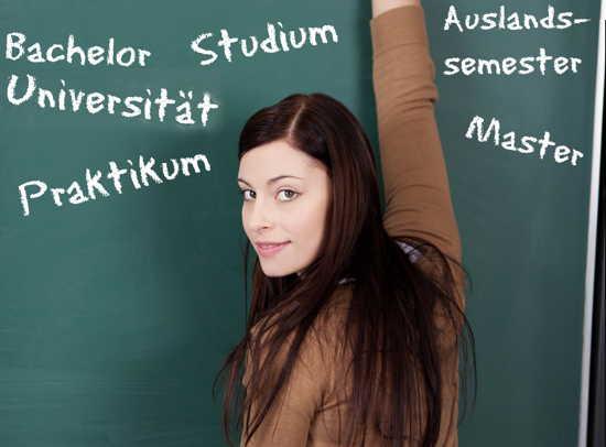 Studentin steht an Tafel, auf der verschiedene Begriffe rund ums Studium stehen.
