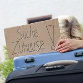 Frau versteckt sich hinter Koffer und hält ein Schild mit der Aufschrift Suche Zuhause hoch