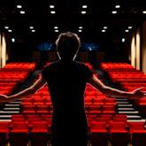 Schauspieler mit ausgebreiteten Armen auf einer Bühne, von hinten fotografiert. Im Hintergrund leere Plätze.