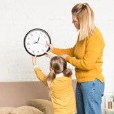 Mutter und Mädchen haben Uhr in der Hand, die sie über einer Couch an die Wand hängen wollen