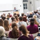 Vortrag in einem Hörsaal, alle Plätze mit Studierenden belegt