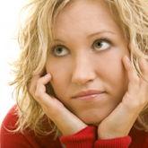 Blonde Frau stützt ihren Kopf auf die Arme, leicht frustrierter Blick