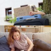 Zwei Bilder nebeneinander: Frau auf bequemer Couch in schöner Wohnung und andere draußen mit Koffern und Schild suche Zuhause